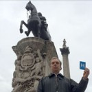 Peter Hitchens holding the letter H, standing with the statues of Nelson and King Charles I