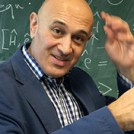 Jim Al-Khalili in front of a blackboard full of maths