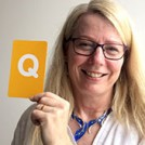 Ruth Scott holding the letter Q