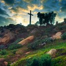 A cross on a hill with clouds