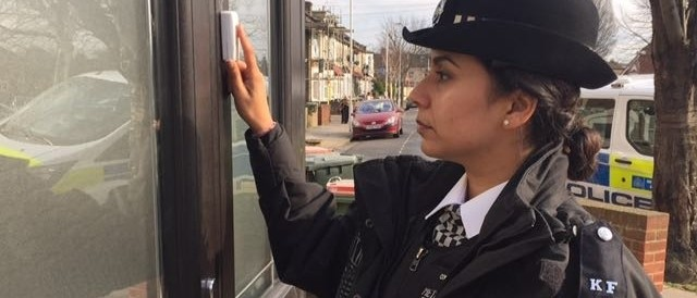 A Police Woman ringing a doorbell