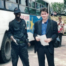 Sasha Chanoff stands next to a hired armed guard in the safe compound outside Kinshasa