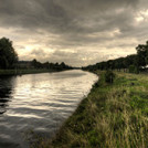 A river, a grassy bank and some dark clouds